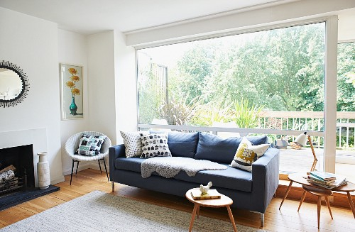 Grey couch and small, wooden fifties side table in front of glass wall
