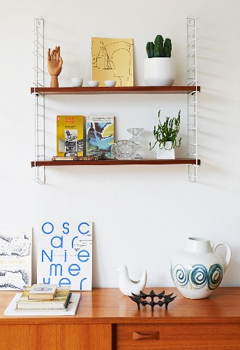 'String' shelves on wall above retro ornaments on partially visible sideboard