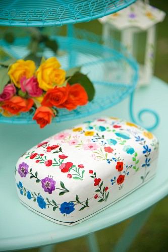 Tin with floral pattern and flowers on turquoise cake stand on garden table