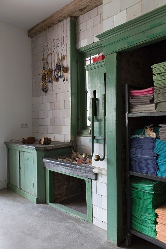 Old, green-painted wooden fittings against tiled wall with decorations hanging from hooks; cloths sorted by colour and stacked in open-fronted cabinet