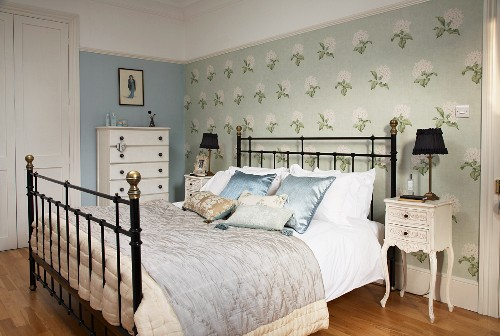 Double bed with black metal lattice frame against accent wall with floral wallpaper