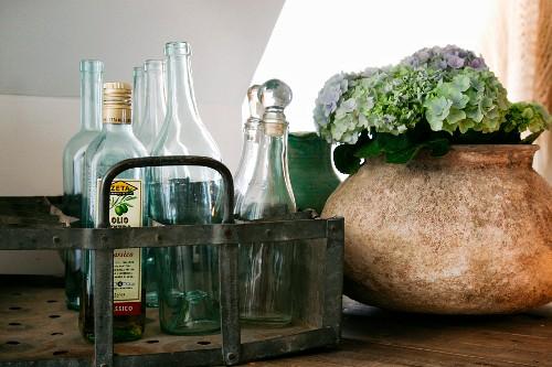 Glass bottles in metal bottle carrier next to ceramic vase of hydrangea flowers