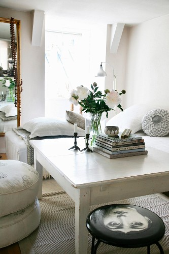 Vase of white peonies on white-painted table in simple living area with stool and stacked floor cushions