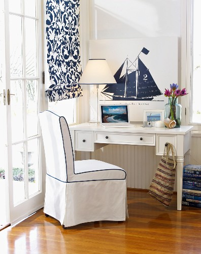 Small white desk in corner of white bedroom with nautical theme