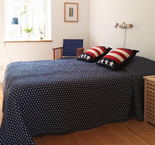 Blue bedspread and stars and stripes scatter cushions on double bed in Scandinavian bedroom