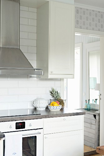 Detail of kitchen counter with white base units and cooker below stainless steel extractor hood