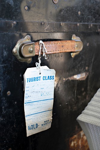 Tag hanging from handle of old leather suitcase