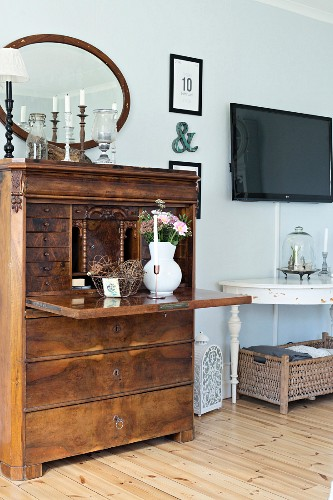 Antique writing desk with vase of flowers on desk panel next to white console table below flatscreen TV on wall in rustic interior