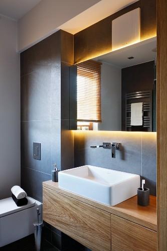 Custom, wooden washstand with countertop basin in grey-tiled niche below backlit mirror