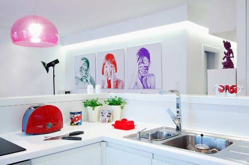 View across white kitchen counter to photo portraits on white wall and pink pendant lamp