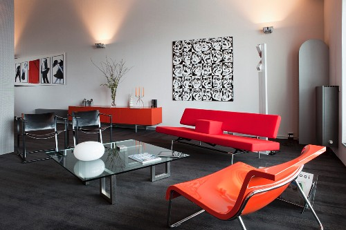 Elegant lounge with seating in mixture of styles and bold shades and sconce lamps in background in loft-style interior