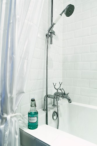 Bathtub with vintage tap fittings and swing-top bottle on rim