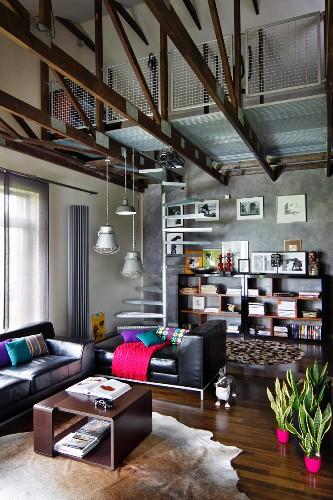 Brauner Couchtisch auf Tierfell, Ledersofagarnitur in Schwarz, in offenem Wohnraum mit sichtbarer Dachkonstruktion, eingebaute Galerie und Wendeltreppe