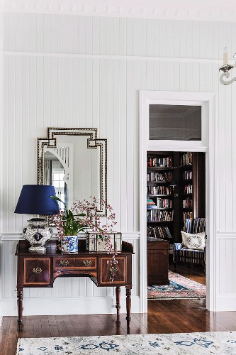 Table lamp with dark blue lampshade and vase of flowers on antique bureau against wood-clad wall and next to open door with view into library