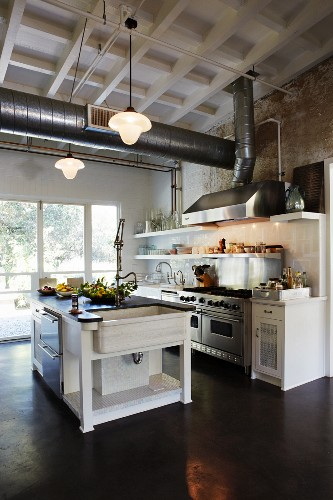 Free-standing counter in open-plan kitchen below ventilation ducts suspended from wooden ceiling