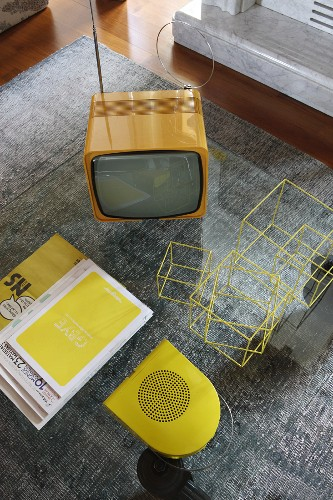 View down onto glass table, fifties-style TV and set of decorative wire cubes