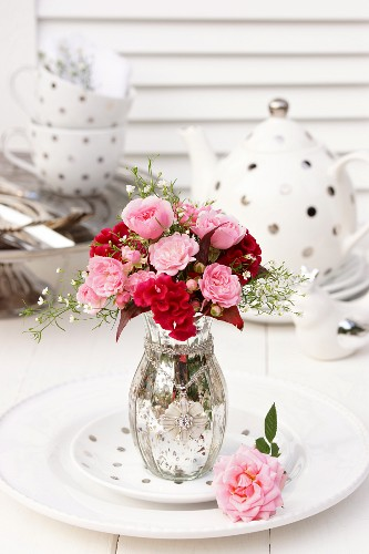 Bouquet of roses with cockscomb and gypsophila in silvered glass vase in front of polka-dot tea set