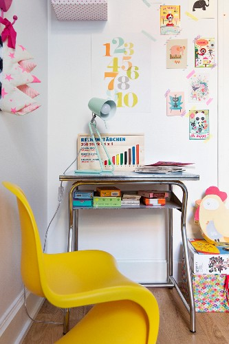 Yellow, child's chair at small desk below postcards and stamped numbers stuck to wall using washi tape