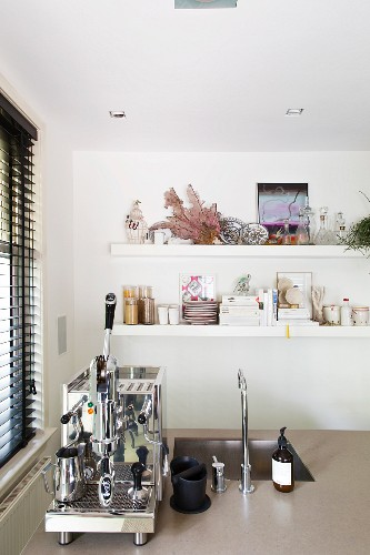 Chrome espresso machine next to sink on counter in front of crockery on wall-mounted shelves