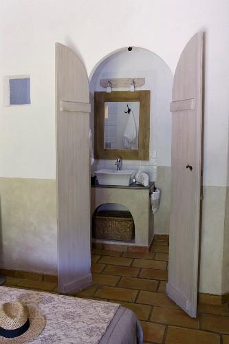 Blick auf gemauerten Waschtisch in Bad Ensuite durch die geöffneten Flügeltür, Bettende mit floral gemustertem Überwurf