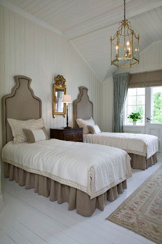 Twin beds with upholstered headboards, brass light fitting and gilt-framed mirror in wood-panelled bedroom