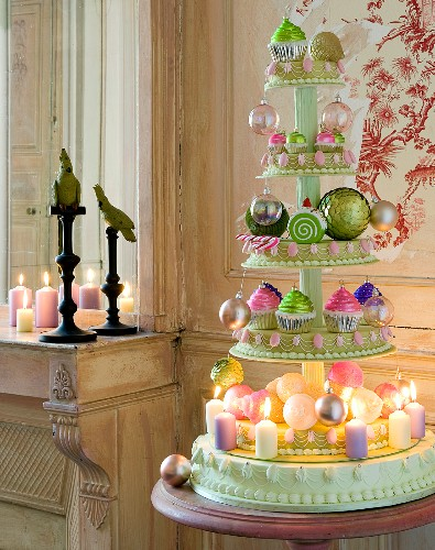 Christmas arrangement of baubles and candles on cake stand