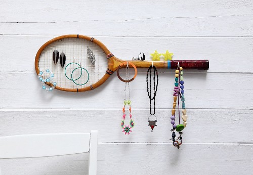 Old tennis racquet mounted on wall as jewellery rack