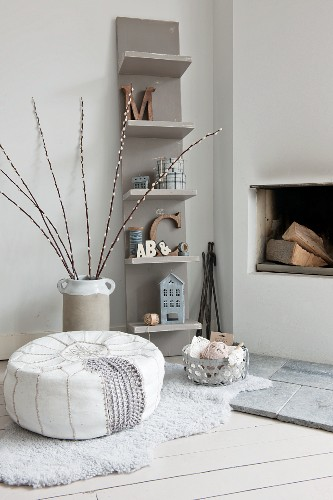 Pouffe and balls of wool in basket on animal-skin rug in front of open fireplace