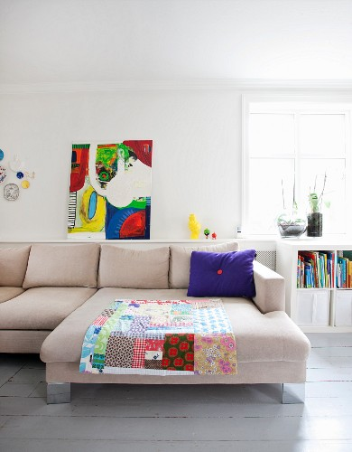 Patchwork blanket and purple scatter cushion on pale sofa combination and modern artwork on shelf leaning against wall