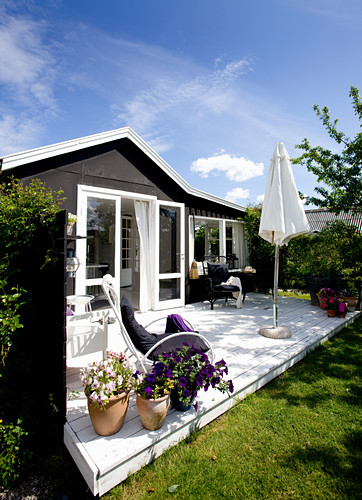 White-painted bamboo chair next to potted violas and petunias on sunny terrace adjoining summer house with white window frames and dark façade