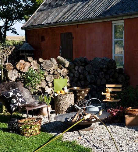 Metal outdoor armchairs and fire bowl on terrace with campfire bread over fire and firewood stacked against house