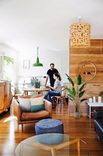 Couple in bright, open-plan interior with dining and lounge areas, parquet floor and modern wood-panelling