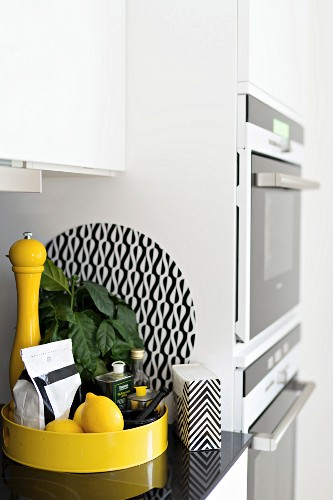 Lemons and condiments on yellow tray on kitchen counter next to cupboards with fitted kitchen appliances