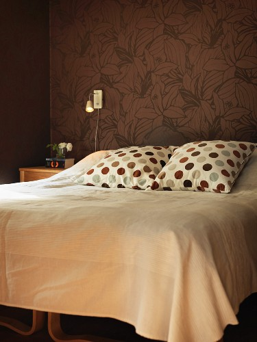 Polka-dot pillows and pale blanket on double bed against brown wallpaper with floral pattern