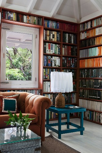 Seating area with caramel-coloured sofa, wicker trunk and petrol blue table in front of full-wall bookcases