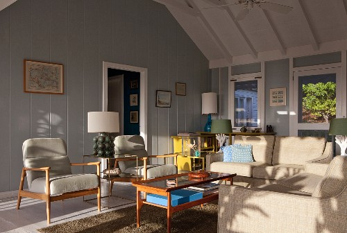 Seating area with 50s, retro furnishings in sunny interior of wooden beach house painted grey and white