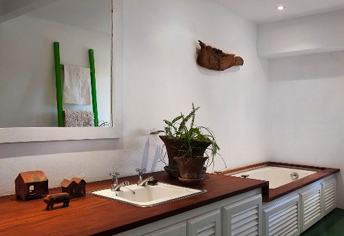 Washstand and bathtub integrated in base cabinets with slatted doors, exotic wood surfaces and ethnic ornaments