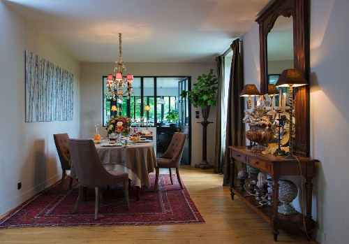 Upholstered chairs around set dining table on Oriental rug and table lamps on antique console table below mirror