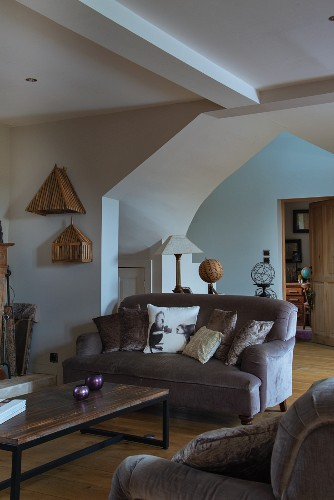 Coffee table and sofa in front of floor-to-ceiling, polygonal arch in rustic interior