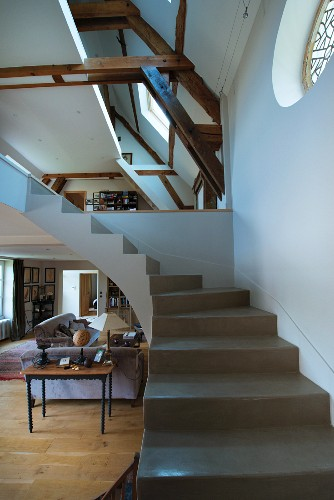 Winding concrete staircase without handrail in interior with converted attic and gallery