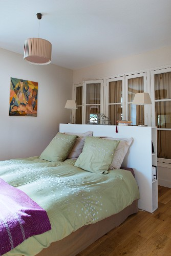 Lime green bed linen and pillows on bed below table lamps on white, modern half-height partition in front of fitted wardrobes with lattice doors