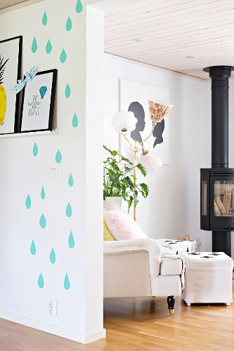 Graphic pattern on wall next to floor-to-ceiling doorway with view of armchair and pouffe in front of log burner