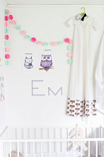 Animal wall stickers and colourful garland next to dress on clothes hanger hung on wall