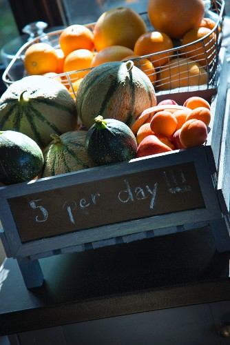 Wooden crate with motto and wire basket holding melons, apricots and oranges