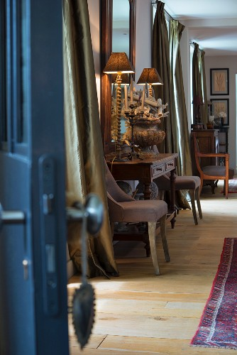 View along corridor: vintage-style table lamps on antique console table flanked by chairs