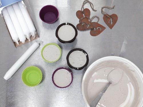 Schüssel mit angerührtem Gips, gefüllte Silikonförmchen, Haushaltskerzen und Zahlenanhänger für selbstgemachten Adventsschmuck