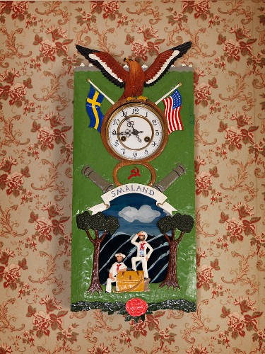 Clock with flag and eagle motifs on painted metal case hung on wall with vintage-style floral wallpaper