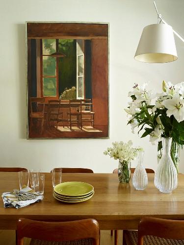 Esstisch aus Eichenholz, darauf Tellerstapel und Glasvasen, mit weißem Lilienstrauss, im Hintergrund an Wand Gemälde