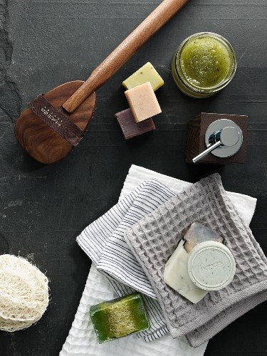 Soaps, towels and other spa utensils on black slate surface
