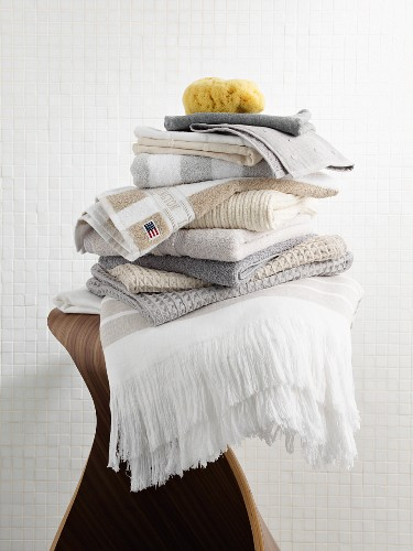 Stack of spa textiles in natural shades on laminate wood stool